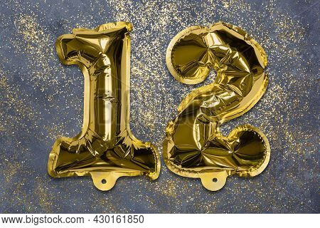 The Number Of The Balloon Made Of Golden Foil, The Number Twelve On A Gray Background With Sequins.