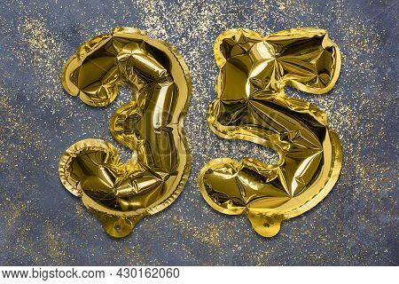 The Number Of The Balloon Made Of Golden Foil, The Number Thirty-five On A Gray Background With Sequ