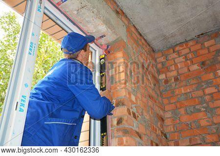 Kyiv, Ukraine - June, 6, 2020: A Window Installer Is Installing A Upvc Window Frame Using A Spirit L
