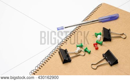 A Notepad With A Used Pen, Black Binder Clips, And Pushpins On White Background With Copy Space
