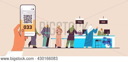 Arab People Looking At Display Number Board In Waiting Room Electronic Queuing System Queue Manageme