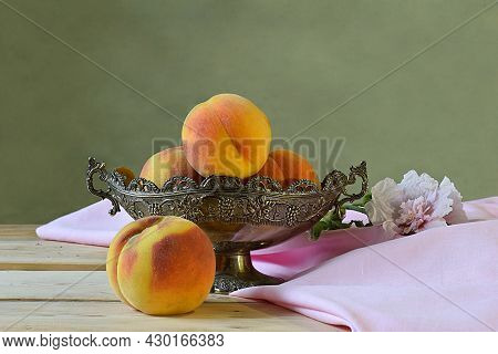 Silver Vase With Peaches And Mallow Flower On A Wooden Table.