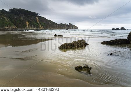 View Of Playa Del Aguilar At Low Tide At Sunset In Asturias In Spain.