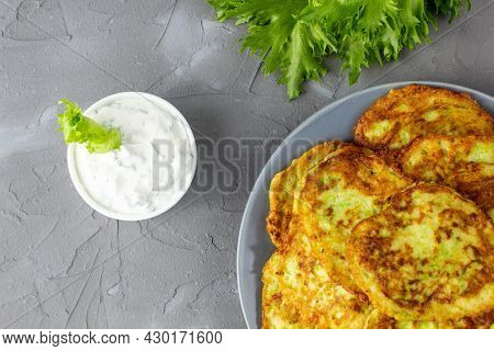 Fritters From Zucchini In Grey Plate With Sour Cream Sauce And Greens. Vegetable Pancakes Of Courget