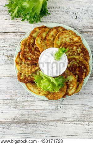 Fritters From Zucchini With Sour Cream Sauce And Greens. Vegetable Pancakes Of Courgettes With Green