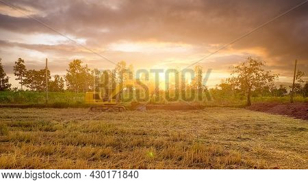 Landscape Of Rice Field And Tropical Forest With Sunset Sky. Backhoe Working By Digging Soil. Excava