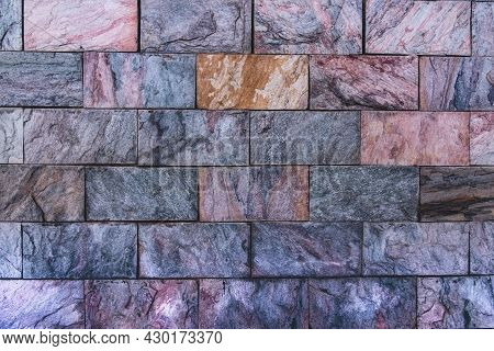 Decorative Wall Cladding With Multi-colored Granite Tiles. Background From Colored Natural Stones. D