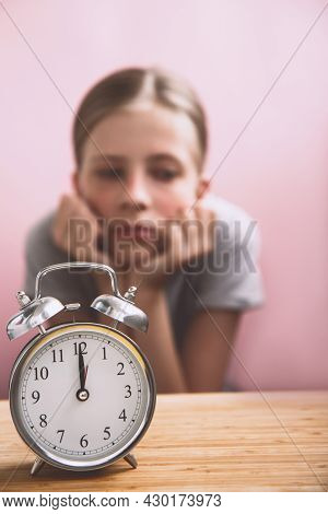 Tired Student With Retro Alarm Clock Preparing For Exams On Bright Pink Background