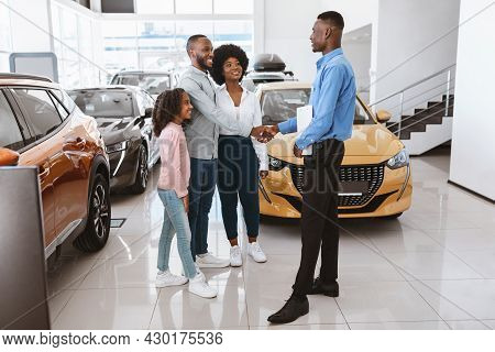 Happy Afro Family Shaking Hands With Car Salesman, Making Auto Purchase Agreement At Dealership