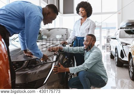 Salesman Talking To Young Black Couple, Showing Them New Luxury Car At Auto Dealership