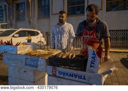Beyoglu, Istanbul, Turkey - 07.07.2021: Two Male Vendors Frying Fish On A Portable Mangal Barbecue O