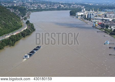Andernach, Germany - July 19th 2021: Rhine During The Summer Flood With A Cargo Ship Passing Anderna