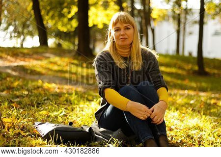 Defocus Nice Blond 40s Woman Seating In Yellow Autumn Park. Happy Beautiful Lady. Women Wearing Grey