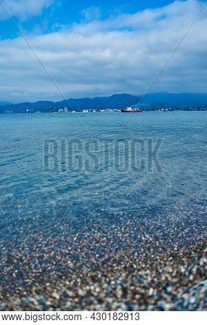 Ship In The Black Sea Off The Coast Of Batumi. Black Sea Water Area Against The Backdrop Of Mountain
