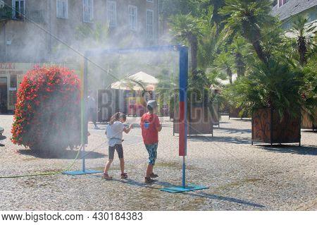 Kudowa Zdroj, Poland - 13. 8. 2021: People Enjoing Street Mist Spreying Device Within A Hot Summer D