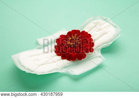 White Sanitary Pad, Hygiene Protection On A Mint Background. Gynecological Menstrual Cycle. A Rose F