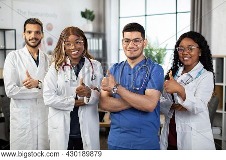 Happy Medical Multiethnic Team Of Four Healthcare Practitioners, Doctors, Interns And Nurses, Showin