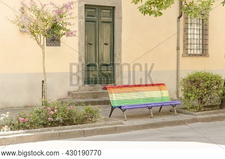 A Rainbow Bench Stands Near The Building And The Roadway
