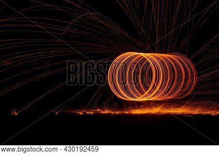 Orange Circle Moving Bright Fire Light Trails On Black Background.
