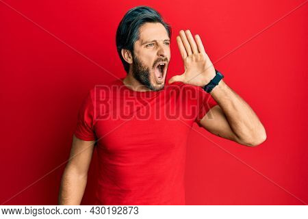 Young hispanic man wearing casual red t shirt shouting and screaming loud to side with hand on mouth. communication concept.