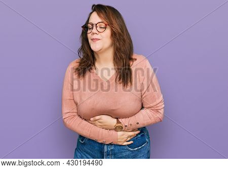 Young plus size woman wearing casual clothes and glasses with hand on stomach because indigestion, painful illness feeling unwell. ache concept.