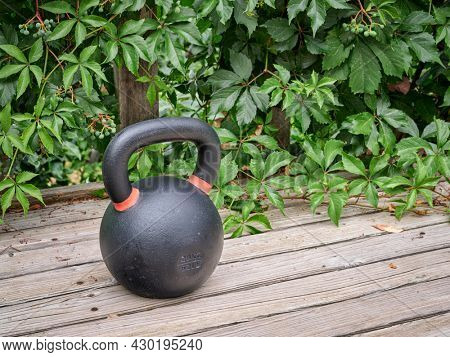 heavy iron competition kettlebell for weight training on wooden grunge deck, home gym and fitness concept