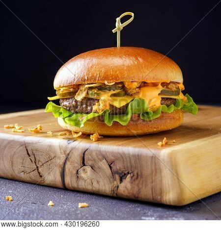 Cheeseburger On A Thick Light Wooden Stand