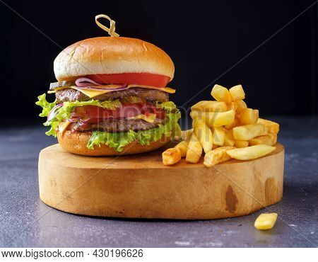 The Hamburger With Two Cutlets On A Light Wooden Board Next To French Fries