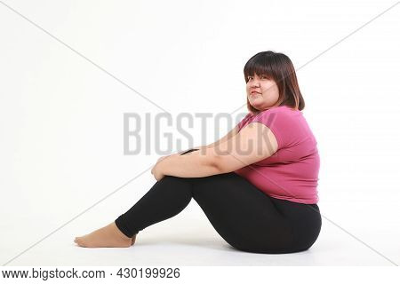 Asian Fat Woman Wear Workout Clothes Sitting On A White Background. Health Care Concept, Weight Loss