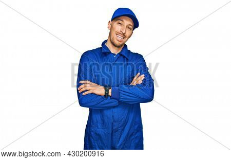 Bald man with beard wearing builder jumpsuit uniform happy face smiling with crossed arms looking at the camera. positive person.