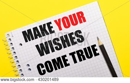 White Notebook With Inscription Make Your Wishes Come True Written In Black Pencil On A Bright Yello
