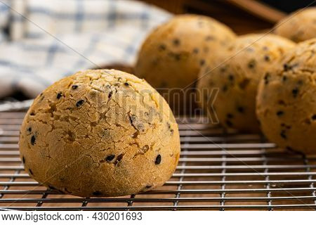 Closeup View Freshly Baked Homemade Sesame Mochi Bun On Metal Cooling Rack With Dish Cloth On Wooden