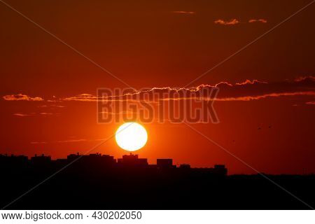 Sunset Over City, Scenic View. Setting Sun And Orange Sky With Dark Dramatic Clouds Above Black Silh