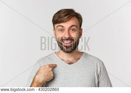 Close-up Of Surprised Handsome Man With Beard, Pointing At Himself And Smiling, Standing Over White