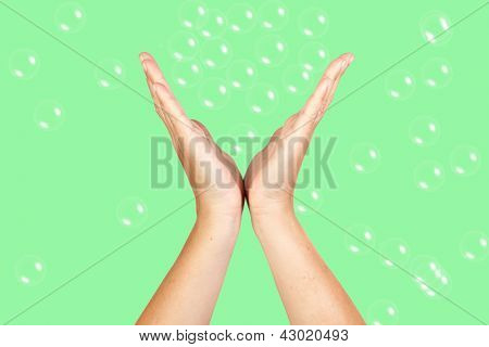 Open Hands catching bubbles on green background