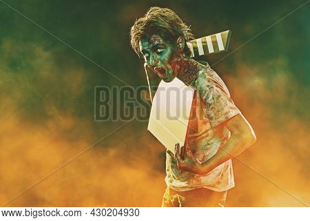 Halloween and Horror movie. Halloween zombie boy teenager holds a clapperboard on dark background with yellow smoke. Copy space.