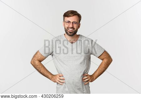 Image Of Confused Bearded Man In Glasses And Gray T-shirt, Looking At Something Strange, Frowning Pe