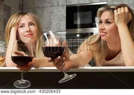 Two Pretty Blonde Women In Evening Dresses Drank Too Much Red Wine From Glasses And Got Drunk. Conse