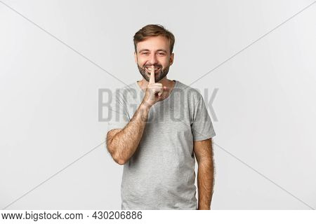 Portrait Of Handsome Smiling Man In Grey T-shirt, Hushing At You Kindly Asking To Keep Quiet, Standi