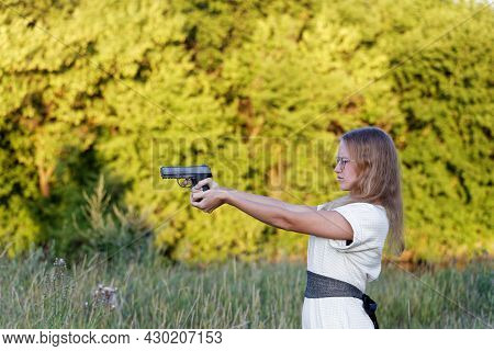 Young Woman Holds A Gun In His Hands And Aim In Target Against Blurred Nature Backgroind. Outdoor Sh