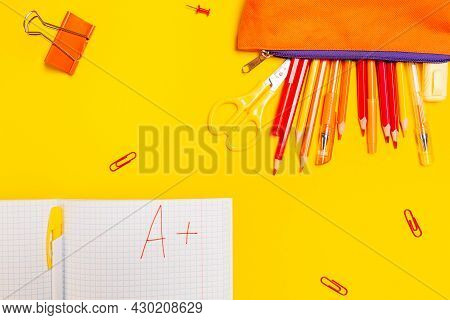 Education. Pencil Box With Pens And Notebook With An Excellent Grade On A Yellow Background With Cli