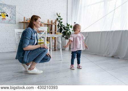 Happy Kindergarten Teacher Looking At Cheerful Disabled Kid In Playroom
