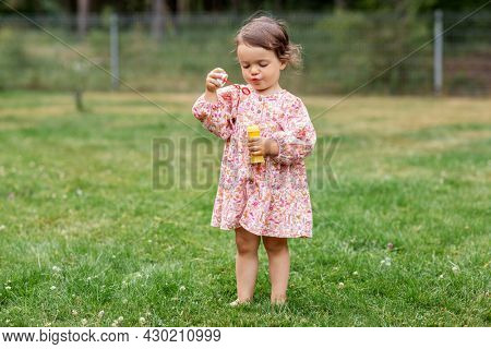 childhood, leisure and people concept - happy little baby girl blowing soap bubbles in summer