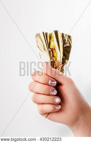 Woman Holding Gold Foil For Manicure. Manicured Nails And Soft Hands Skin Wide Banner. Beauty Treatm