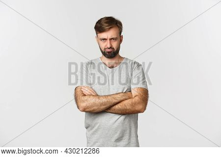 Portrait Of Offended Handsome Man, Sulking And Making Angry Grimace, Cross Hands Over Chest Defensiv