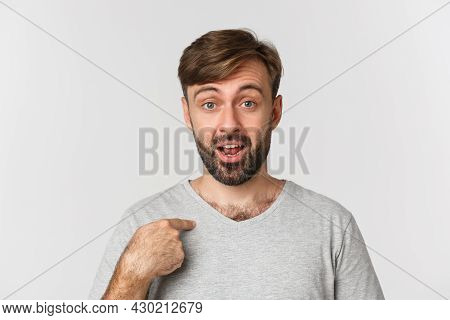 Close-up Of Surprised Handsome Man With Beard, Pointing At Himself And Looking Confused, Standing Ov