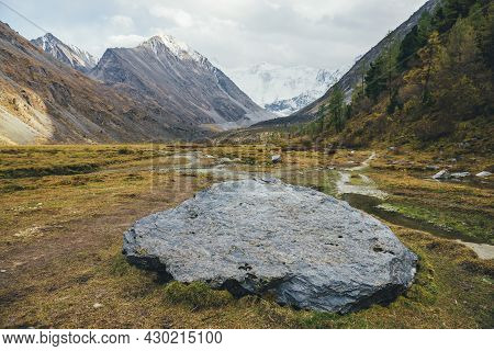 Scenic Landscape With Big Stone In Sunlit Golden Valley In Autumn Colors With View To High Snowy Mou