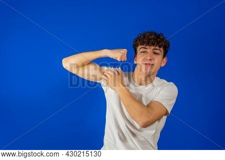Proud Man Pointing At His Biceps And Looking At Camera. Portrait Of Handsome Hipster Curly Young Man