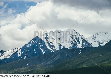 Awesome Mountains Landscape With High Snowy Mountain Range Among White Clouds In Blue Sky. Atmospher
