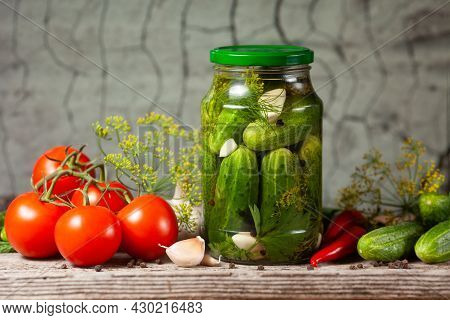 Pickled Cucumbers In Glass Jars And Spices And Vegetables For Preparation Of Pickles On Old Stone Wa